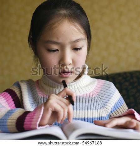 ten-year old asian schoolgirl studying