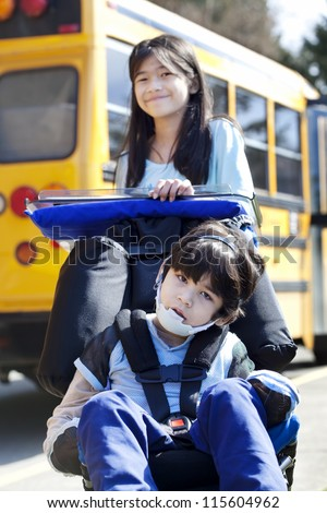 Ten year old girl  pushing disabled little boy wearing protective gear  in wheelchair  next to school bus. Child has cerebral palsy.