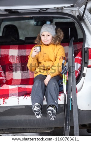 Ten years child sits in trunk of car, drinks hot tea after skiing in wintry woods #1160783611