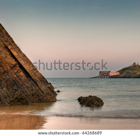 Tenby, Wales Clear Sky Sunset - view out to sea from Tenby, Wales beach - large rock in foreground, lifeguard stations in background - stock photo