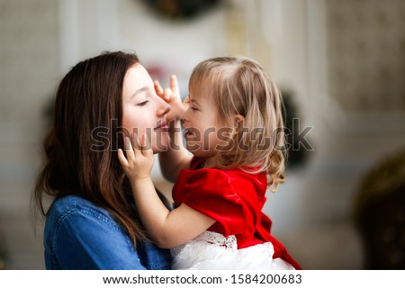 tender Caucasian sisters, girl with down syndrome and sister teenager, sister hugs, cares, touches a child with disabilities, concept childhood and sisters relationship