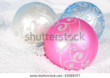 Tender Christmas bauble of rose, blue and white color on to snow.