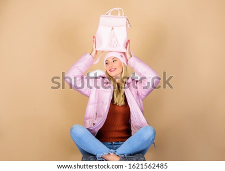 Tender combination. Matching accessories. Fashion accessory. Girl adorable model showing her fancy leather backpack. Backpack is all you need. Little backpack and knitted hat. Total pastel outfit.