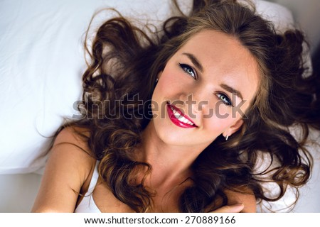 Tender fashion morning portrait of stunning young sexy woman with freckles fluffy hairs and bright make up, lay and relax on the bed, cute smiling positive face and emotions, soft colors.