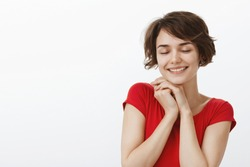 Tender feminine gentle cute woman short haircut touch hands together near shoulder close eyes admiration lovely tenderness smiling remember heartwarming moment dreaming white background