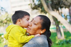 Tender portrait of little son kissing his mommy.