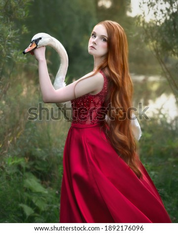 Tender red-haired girl with a white swan