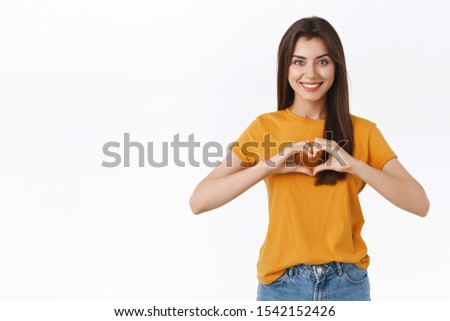 Tender, romantic and happy brunette woman in yellow t-shirt, showing heart or love sign and smiling, cherish relationship, confess in affection or admiration, standing white background cheerful