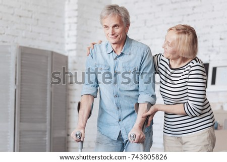 Tender senior lady taking care of husband on crutches