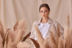 Tender soft studio portrait of elegant female model posing between ears of rye at textile background. Girl in brown skirt and beige jacket. Young woman with brunnette hair in pony tail