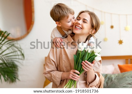 tender son kisses the happy mother and gives her a bouquet of tulips, congratulating her on mother's day during holiday celebration at home