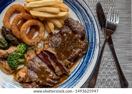 Tender steak Moderate Topped with juicy juicy gravy, tasty Served with French Fries and Crispy Onion Rings Along with the salad Is a menu that provides value and high protein., Braised Beef Steak #1493625947