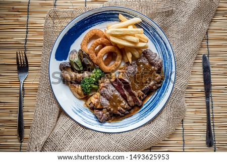Tender steak Moderate Topped with juicy juicy gravy, tasty Served with French Fries and Crispy Onion Rings Along with the salad Is a menu that provides value and high protein., Braised Beef Steak #1493625953