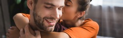 tender woman embracing happy boyfriend and whispering in his ear, banner