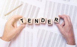 TENDER word on wooden cubes on office table full of financial documents.
