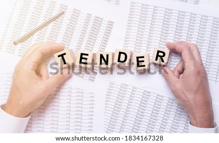 TENDER word on wooden cubes on office table full of financial documents. Stock photo ©