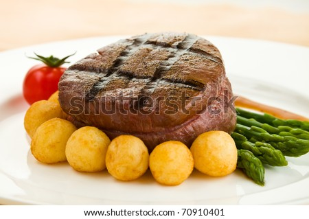 Tenderloin steak in a white plate with vegetable. Shallow depth of field.