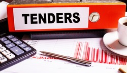 TENDERS is written on a red document folder near a pen, calculator, coffee cup and graphs.