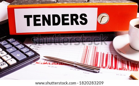 TENDERS is written on a red document folder near a pen, calculator, coffee cup and graphs. Stock photo ©