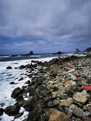 Tenerife North Coast - Rugged volcanic shoreline of Playa del Roque de las Bodegas and surrounding under tormented rainy weather