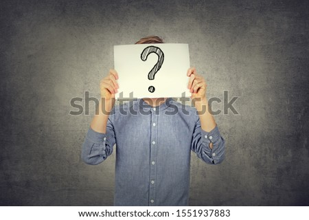 Tennager Boy using a white paper with drawn question mark on gray wall background. Question mark, symbol. Pensive male. Getting answers. Doubtful man holding Question Mark. Problems and solutions.