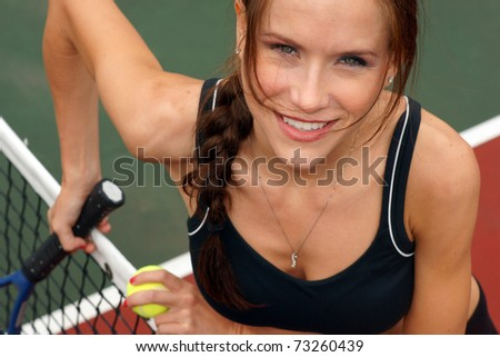 Tennis Anyone Attractive Woman Comes to the Net Holding Racquet Ball Smiling