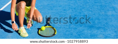 Tennis athlete player on getting ready tying running shoe laces during game on outdoor blue hard court. Banner panorama.