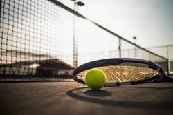 Tennis ball and racket on hard court under sunlight