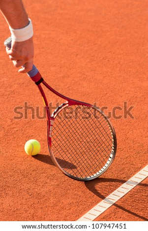 tennis ball and racket on the red clay court