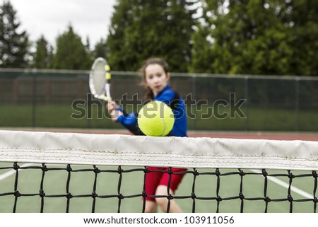 Tennis ball barely clearing the net with female player rushing to net