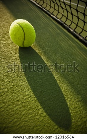 tennis ball casting shadow on court near net