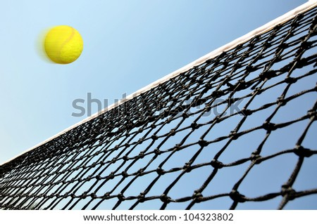 Tennis  ball flying over the net under the blue sky.