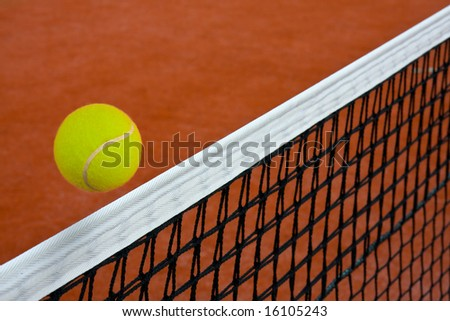 Tennis ball gliding over the net on clay court