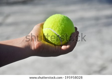 Tennis ball in his hand. The hand of the child squeezes yellow-green tennis ball against a light background.