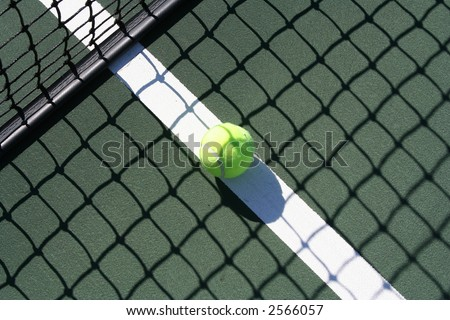 Tennis ball in the shadow of the net