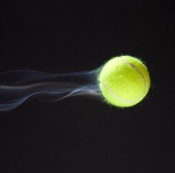Tennis ball moving fast giving illusion of smoke behind it.