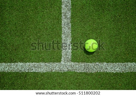 Stock Photo Tennis ball near the line on tennis grass court from top view. Good for background