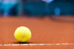 tennis ball on a clay court, close to the fault line