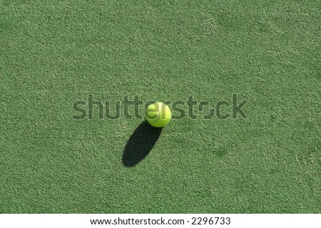 Tennis ball on a green artificial court surface,natural lighting and shadows.
