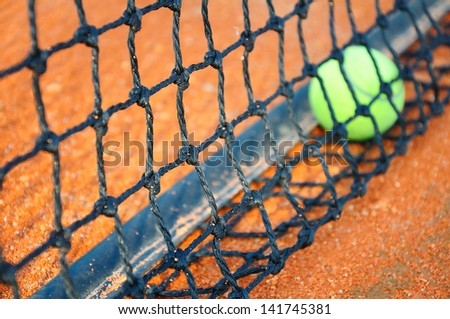 Tennis ball on a tennis clay court (Focus on net)