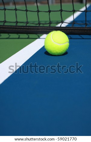 Tennis ball on blue court at the net