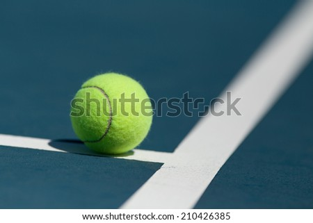 Tennis ball on blue hard court inside of line
