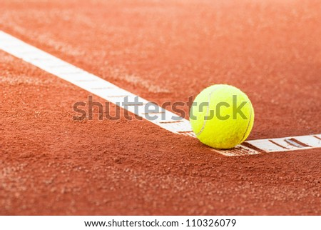 tennis ball on clay court - stock photo