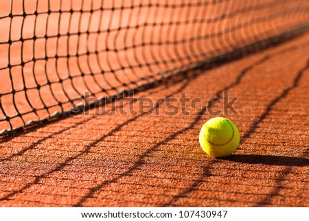 tennis ball on court just behind the net