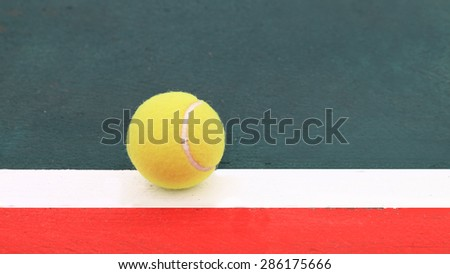 Tennis ball on green painted white line and the floor outside the red zone.