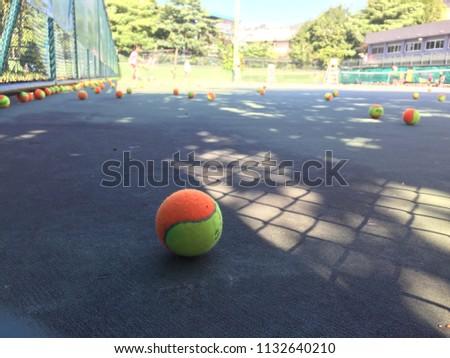 Tennis ball on hard court under sunlight