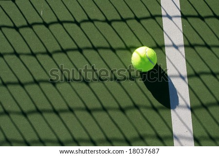 Tennis ball on the court in the shadow of the net