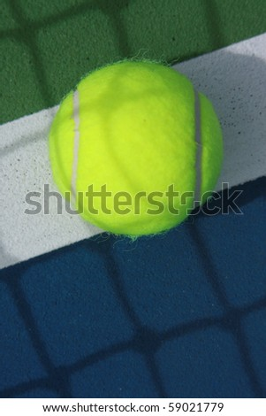 tennis ball on the inbound line on blue tennis field