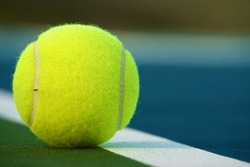 Tennis ball on the line close-up. Could be in our out. Close call.
