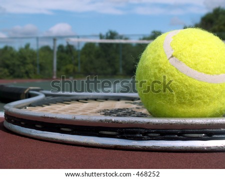tennis ball resting on a raquet at the edge of a tennis court.
